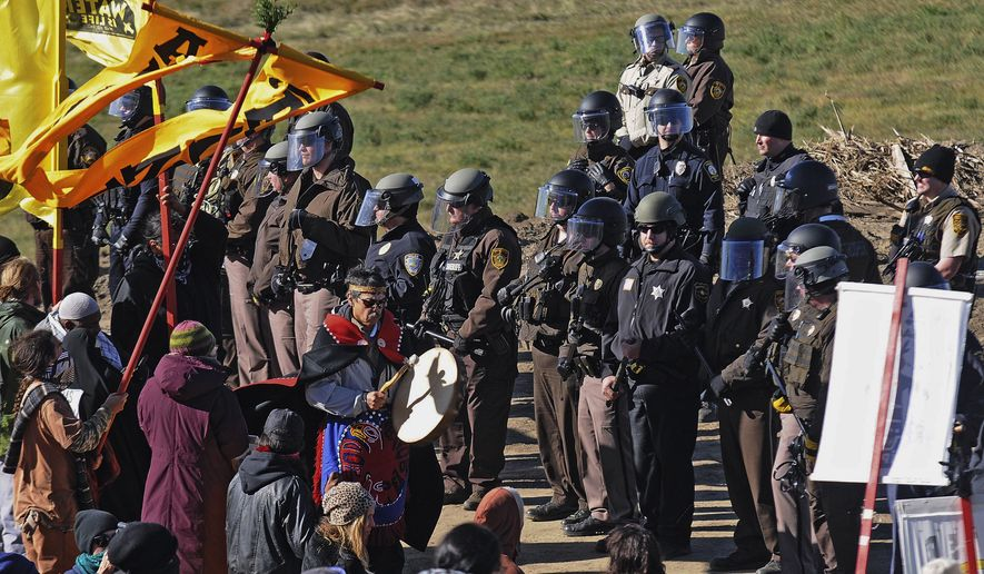 A person with a hand drum paces between law enforcement officers and a line of protesters along North Dakota Highway 6, south of St. Anthony, N.D., Monday, Oct. 10, 2016. The U.S. Army Corps of Engineers won't yet authorize construction of the $3.8 billion, four-state Dakota Access oil pipeline on federal land in southern North Dakota, it said Monday, along with reiterating its earlier request that the pipeline company voluntarily stop work on private land in the area. (Tom Stromme/The Bismarck Tribune via AP)