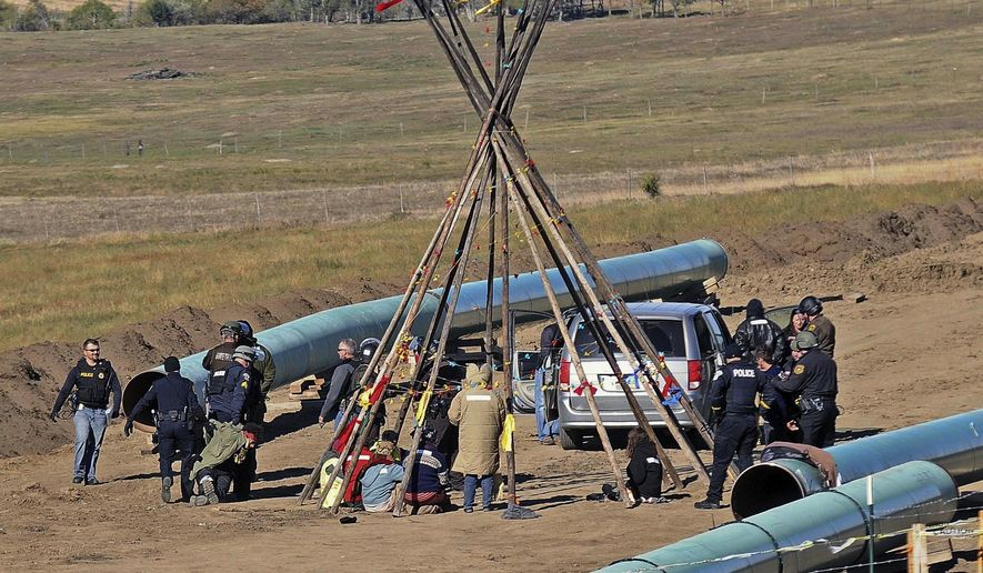 Law enforcement officers, left, drag a person from a protest against the Dakota Access Pipeline, near the town of St. Anthony in rural Morton County, N.D., Monday, Oct. 10, 2016. The U.S. Army Corps of Engineers won't yet authorize construction of the $3.8 billion, four-state Dakota Access oil pipeline on federal land in southern North Dakota, it said Monday, along with reiterating its earlier request that the pipeline company voluntarily stop work on private land in the area. (Tom Stromme/The Bismarck Tribune via AP)