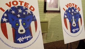 """Louisiana voters will receive """"I VOTED"""" stickers featuring George Rodrigue's iconic Blue Dog when they turn out at early voting sites or at their polling locations on Election Day. Secretary of State Tom Schedler unveiled the stickers Monday, Oct. 10, in Baton Rouge, La. (AP Photo/Melinda Deslatte)"""