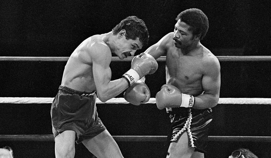 FILE - In this Nov. 12, 1982, file photo, Alexis Arguello covers up as defending champ Aaron Pryor throws a hard right during the second round of boxing action at the Orange Bowl in Miami. Pryor, the relentless junior welterweight died Sunday, Oct. 9, 2016, at the age of 60. Pryor's family issued a statement saying the former boxer died at his home in Cincinnati after a long battle with heart disease. (AP Photo/File)