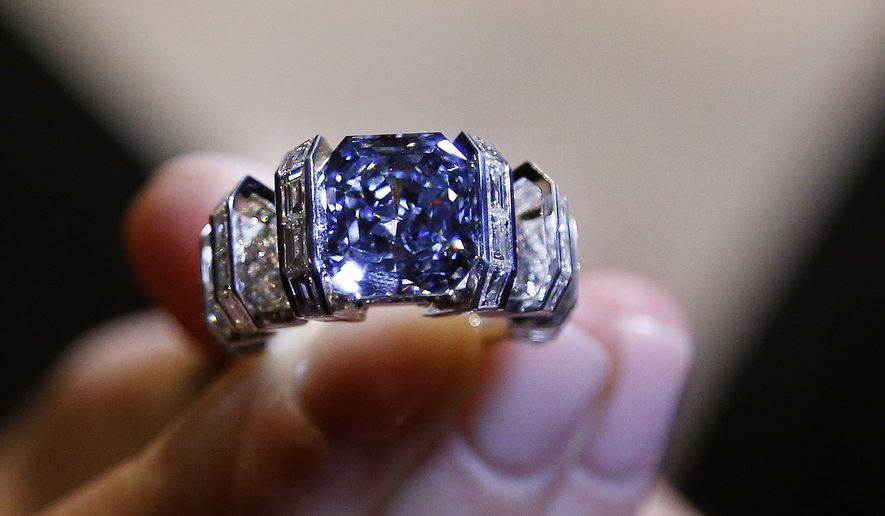 A model shows 'The Sky Blue Diamond' ring at the auction house Sotheby's in London, Tuesday, Oct. 11, 2016. The mesmerizing and rare vivid blue diamond weighs 8.01 carats, mounted by Cartier, will be on auction on Nov. 16, 2017 with an estimate of 15-25 million dollars (12-20 million pounds, 13.5-22.5 million euro). (AP Photo/Frank Augstein)