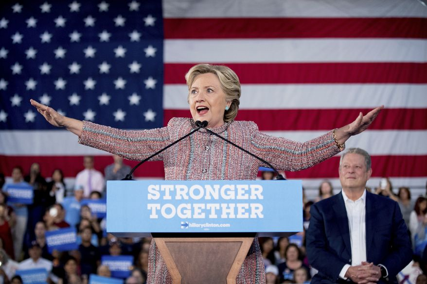Democratic presidential candidate Hillary Clinton, accompanied by former Vice President Al Gore, right, attempts to quiet the crowd as a protester disrupts her speech during a rally at Miami Dade College in Miami, Tuesday, Oct. 11, 2016. (AP Photo/Andrew Harnik)