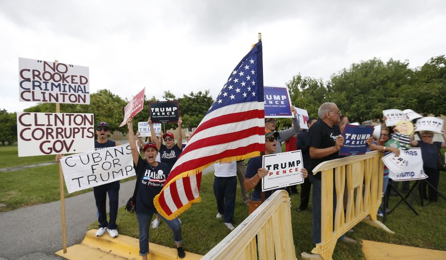 Supporters of Republican presidential candidate Donald Trump demonstrate outside a rally for Democratic presidential candidate Hillary Clinton, and former vice president Al Gore, Tuesday, Oct. 11, 2016, in Miami. During the event, Clinton will emphasizing her plans to develop more clean energy, reduce fossil fuel production and build more weather-resistant infrastructure. (AP Photo/Wilfredo Lee)