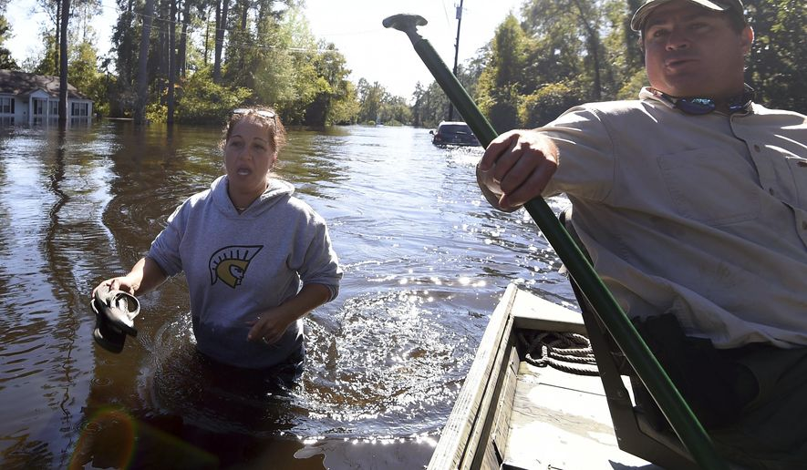 Natalie McDowell, left, speaks with Rawlings LaMotte as she walks to her flooded home on Tuesday, Oct. 11, 2016, in Nichols, S.C. About 150 people were rescued by boats from flooding in the riverside village of Nichols on Monday. (AP Photo/Rainier Ehrhardt)