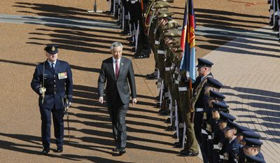 Prime Minister of Singapore, Lee Hsien Loong, center, is formally welcomed to the Australian Parliament in Canberra, Wednesday, Oct. 12, 2016. Prime Minister Lee inspected a guard of honour in the Parliament House Forecourt. Prime Minister Lee is on a 2-day visit to Australia. (AP Photo/Sean Davey)