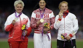 FILE - In this file photo dated Saturday, Aug. 11, 2012, Russia's Tatyana Lysenko is flanked by Poland's Anita Wlodarczyk, left, and Germany's Betty Heidler on the podium for the women's hammer throw event in the Olympic Stadium at the 2012 Summer Olympics, in London. The IOC says Tuesday Oct. 11, 2016, Lysenko tested positive for the steroid turinabol in reanalysis of her stored samples, has been retroactively disqualified from the London Olympic games, and stripped of her gold medal. (AP Photo/Matt Slocum, FILE)