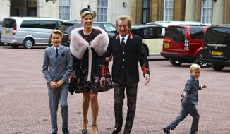 Veteran singer Sir Rod Stewart arriving at Buckingham Palace in London, with his wife, Penny Lancaster and children Alastair and Aiden, ahead of him receiving his knighthood in recognition of his services to music and charity, Tuesday, Oct. 11, 2016. (Gareth Fulller/Pool Photo via AP)