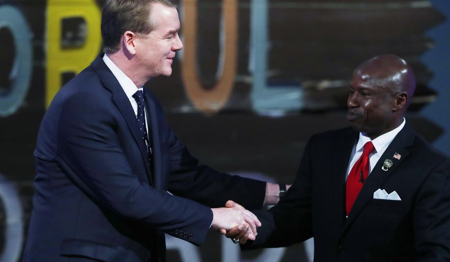 U.S. Sen. Michael Bennet, D-Colo., left, shakes hands with Republican U.S. Senate candidate Darryl Glenn at the conclusion of their televised debate at History Colorado late Tuesday, Oct. 11, 2016, in Denver. (AP Photo/David Zalubowski)