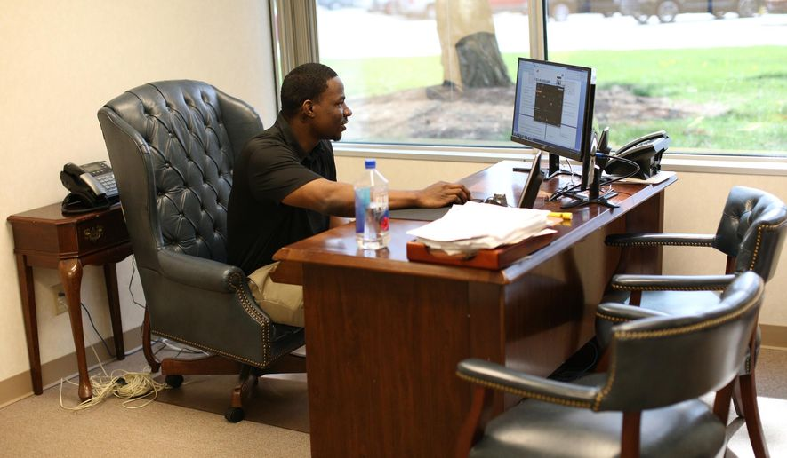In an April 18, 2016 photo, Omar Pouncy, 28, works in his office as the chief of appeals with his lawyer David L. Moffitt, at his law office in Bingham Farms, Mich. Pouncy, a Michigan inmate who was released in March after 10 years in prison when a federal judge found he had been wrongfully convicted of carjacking, armed robbery and other charges is back behind bars. Pouncy was booked Sept. 23 on a charge of being a felon in possession of a firearm.  (Kimberly P. Mitchell/Detroit Free Press via AP)