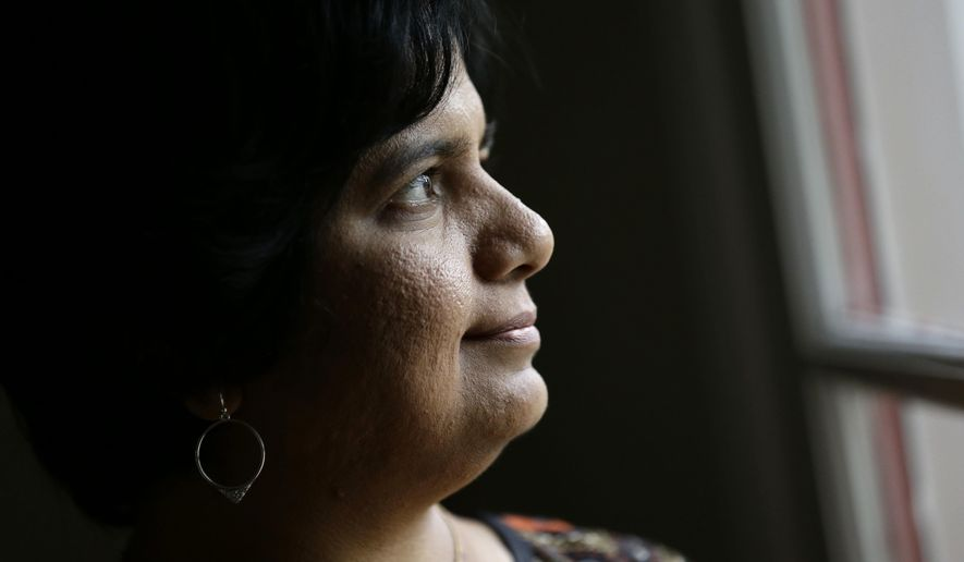HOLD FOR RELEASE UNTIL 12:01 A.M., WEDNESDAY, OCT. 12, 2016, AND THEREAFTER - In this Friday, Sept. 16, 2016, photo, Manasi Gopala, a software developer in North Carolina's Research Triangle, peers out of her back door in Cary, N.C. She left her birthplace of Bangalore, India in 2002, even as many Americans lamented the outsourcing of tech jobs to that city. Gopala arrived in the United States on a marriage visa and promptly obtained a master's degree in computer engineering. She became a citizen in 2013. (AP Photo/Gerry Broome)