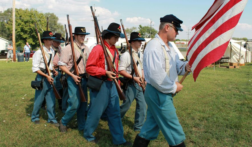 In this Sept. 24, 2016 photo, Downs, Ill., based Civil War re-enactors of  Company D, 21st Illinois Infantry Regiment, march during a drill demonstration as a part of Grant Days in Mattoon, Ill. Their re-enactments vary in size and scope. There can be about seven to 10 guys portraying an encampment, or, there can be a group of over 18 representing a unit in a battle re-enactment. at the Civil War Memorial Ellipse and Camp Grant Municipal Park. (Jarad Jarmon/Journal Gazette via AP)