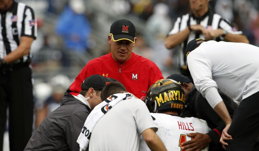 Maryland NCAA college football head coach DJ Durkin, rear, looks on as quarterback Perry Hills (11) is tended to after being injured during a game against Penn State in State College, Pa., Saturday, Oct. 8, 2016. Maryland's smooth ride under coach DJ Durkin has been interrupted by a lopsided defeat and an injured quarterback. (AP Photo/Chris Knight)