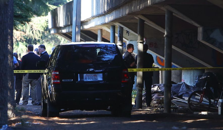 """Police investigate the scene of an officer-involved shooting on Tuesday, Oct. 11, 2016, at Airport Way South and South Bayview Street, near the """"Jungle"""" homeless encampment that was being cleared out to relocate its residents. (Genna Martin/seattlepi.com via AP)"""