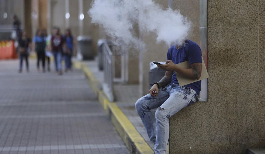 A Filipino uses an electronic cigarette outside a mall in Manila, Philippines Tuesday, Oct. 11, 2016. Health Secretary Paulyn Ubial said Tuesday she hopes Philippine President Rodrigo Duterte can sign the draft executive order banning smoking in public nationwide before the end of the month. She also said e-cigarettes will be included in the ban. (AP Photo/Aaron Favila)