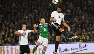 Germany's Sami Khedira, right, heads for the ball in front of Northern Ireland's Lee Hodson, center, and Germany's Mario Goetze, left, during the World Cup Group C qualifying soccer match between Germany and Northern Ireland in Hannover, Germany, Tuesday, Oct. 11, 2016. (AP Photo/Martin Meissner)