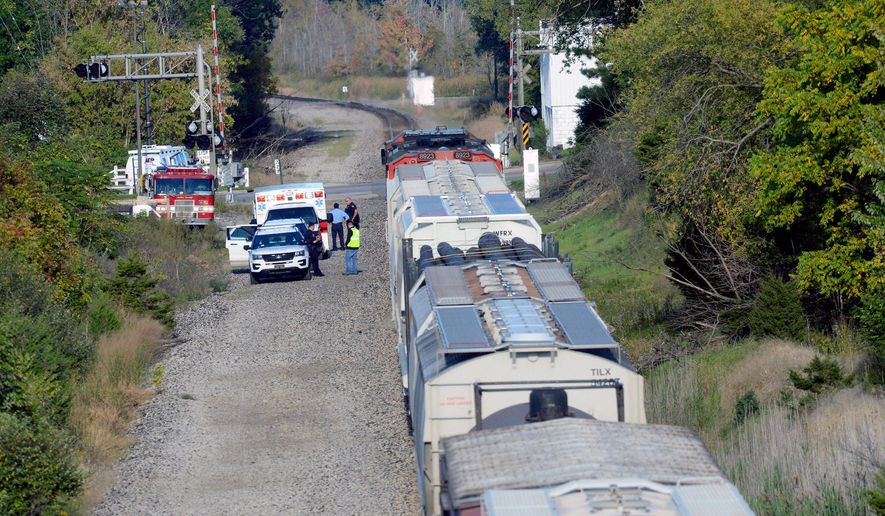 In this Monday, Oct. 10, 2016 photo, emergency crews investigate a fatal train crash near the intersection of Haslett and Marsh roads in Haslett, Mich. Authorities say a 13-year-old boy has died after being struck by a freight train in the Lansing area. (Dave Wasinger/Lansing State Journal via AP)