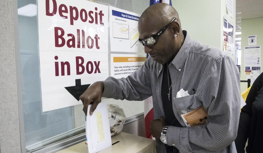 James Chambers deposits his vote into a ballot box at the Hamilton County Board of Elections as early voting begins statewide, Wednesday, Oct. 12, 2016, in Cincinnati. (AP Photo/John Minchillo)