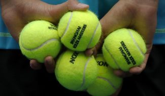 A ball boy holds tennis balls during the men's singles match between Stan Wawrinka of Switzerland and Kyle Edmund of Britain in the Shanghai Masters tennis tournament at Qizhong Forest Sports City Tennis Center in Shanghai, China, Wednesday, Oct. 12, 2016. (AP Photo/Andy Wong)