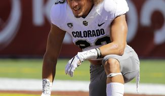 FILE - In this Saturday, Oct. 8, 2016, file photo, Colorado 's Phillip Lindsay kneels on the field during warmups before an NCAA college football game against Southern California in Los Angeles.  His nickname: Tasmanian Devil. His hair: Everywhere. His running style: A combination of the two.  The Colorado junior is a tailback who fell through the recruiting cracks, landed in Boulder and has emerged as a leader. (AP Photo/Jae C. Hong, File)