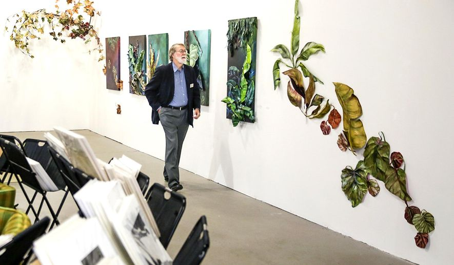 In this Sept. 21, 2016 photo, Gallery Seven vistor Jon Balke walks past a series  of leaf sculptures and paintings in Joliet, Ill. Gallery Seven was one of four galleries that opened in storefront space available at the Rialto Square Theatre in an attempt to create some synergy between the local art community and the theater. (Eric Ginnard/Herald News via AP)