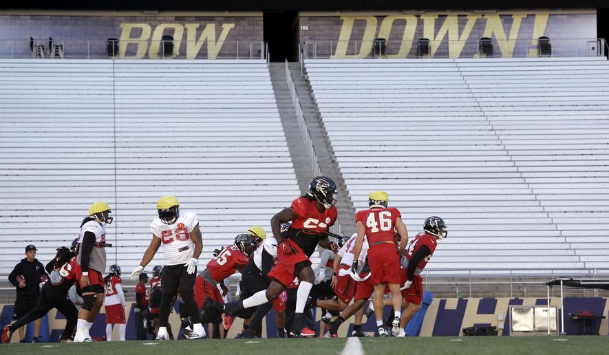 Atlanta Falcons players run through a drill below a slogan for the University of Washington during a practice at the school Wednesday, Oct. 12, 2016, in Seattle. Rather than head home, the team traveled directly to Seattle after a football game Sunday in Denver, ahead of playing the Seattle Seahawks this coming Sunday in Seattle. (AP Photo/Elaine Thompson)