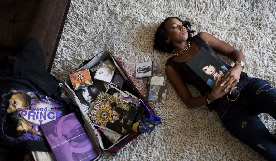 """Margo Davis poses for a portrait as she lays next to a collection of Prince memorabilia at her home in Smyrna, Ga., Tuesday, Oct. 11, 2016. Nearly 6 months after the legendary Prince was found dead in an elevator at his beloved Paisley Park, superfans are still in mourning. """"It's a spiritual connection for me,"""" Davis said. """"I had to leave work when he passed. I didn't turn on the TV or pay attention to any of the tributes. I'm finally able to listen, but in a very limited way."""" (AP Photo/David Goldman)"""