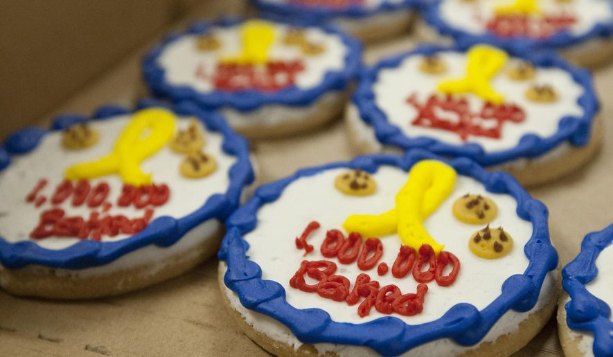 Celebratory cookies honoring the Iowa Cookie Crumbs organization's millionth cookie baked and packaged to send to U.S. military personnel deployed overseas sit for volunteers at Emanuel Lutheran Church in Council Bluffs, Iowa, after the group boxed up thousands of cookies on Tuesday, Oct. 12, 2016. (Joe Shearer/Daily Nonpareil via AP)
