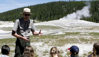 ADVANCE FOR WEEKEND USE OCT. 15, 2016 AND THEREAFTER - In this Thursday, July 7, 2016 photo, Yellowstone National Park ranger Mike Vogel talks about the science behind Old Faithful's eruptions from the boardwalk around the geyser in Yellowstone National Park in Wyoming. Working for the National Park Service can be a calling or a quest for adventure, but for most, wearing the uniform produces a sense of pride. (Raymond Hillegas/The Cody Enterprise via AP)