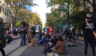 Protesters sit on the street after clashing with Portland police outside City Hall in Portland, Ore., Wednesday, Oct. 12, 2016. The Portland City Council approved a new police contract in a conference room that was blocked off from the general public because of protests that led to arrests. (Brad Schmidt/The Oregonian via AP)