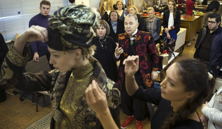 In this photo taken on Tuesday, Feb. 16, 2016, Russian designer Slava Zaitsev, center back, makes comments during fitting at his House of Fashion in Moscow, Russia. At 78, fashion designer Slava Zaitsev may look frail and complain that he left his cane at home but he still makes two new collections every year, one of which premieres at the Russian Fashion Week on Thursday, Oct. 13, 2016. (AP Photo/Pavel Golovkin)