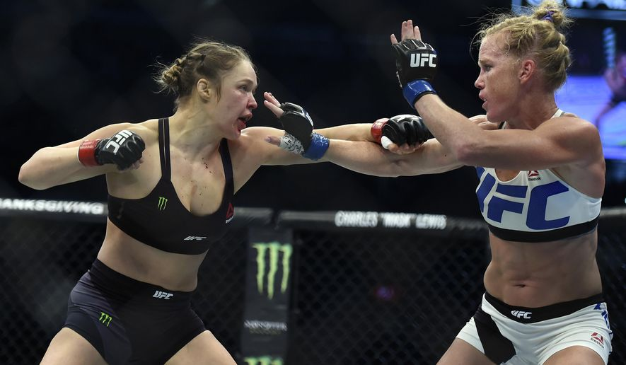 FILE - In this Nov. 15, 2015, file photo, Ronda Rousey, left, and Holly Holm fight during their UFC 193 bantamweight title bout in Melbourne, Australia. Rousey will return to the UFC on Dec. 30 in Las Vegas, fighting Amanda Nunes for the bantamweight title. (AP Photo/Andy Brownbill)