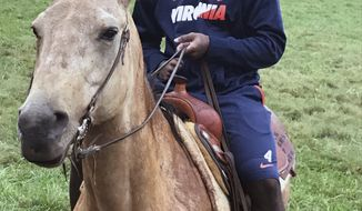 This photo provided by Jack McDonald shows University of Virginia football player Taquan Mizzell riding a horse at Virginia head coach Bronco Mendenhall's ranch in Charlottesville, Va., Saturday, Oct. 8, 2016. Virginia had a bye week with intense practices as if there was a game to be played. And then, the Cavaliers went horse-back riding. (Jack McDonald via AP)