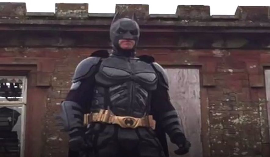 """A British man from Cumbria dresses as Batman to scare away people dressed as """"creepy clowns."""" The campaign has been put together by a group called """"Cumbria Superheroes"""" to make children feel safe. (BBC screenshot)"""