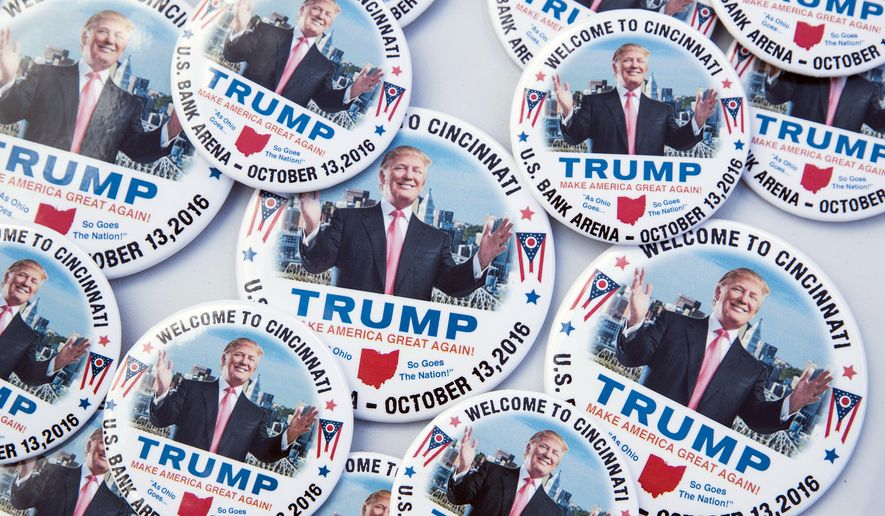 Campaign buttons in support of Republican presidential candidate Donald Trump rest on a vendor table before a campaign rally at US Bank Arena, Thursday, Oct. 13, 2016, in Cincinnati. (AP Photo/John Minchillo)