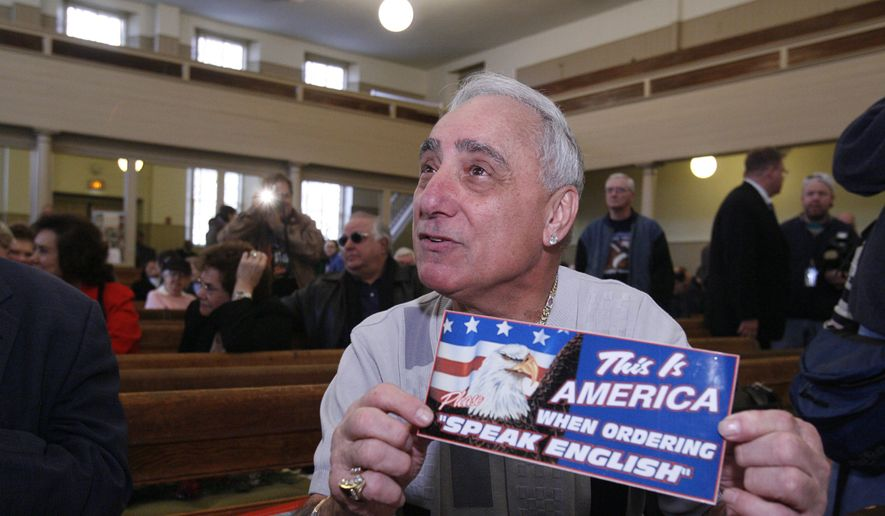 Joseph Vento, owner of Geno's Steaks in Philadelphia, displays a sign that was displayed at his restaurant during a recess of a Commission on Human Relations hearing in Philadelphia, Dec. 14, 2007. The landmark Philadelphia cheesesteak stand has removed the sign posted a decade ago that told customers to order only in English. (AP Photo/Matt Rourke, File) ** FILE **