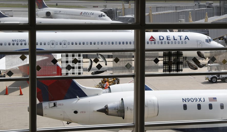 In this Monday, Aug. 8, 2016, file photo, Delta Air Lines planes are parked at Ronald Reagan Washington National Airport, in Washington. Delta Air Lines reports financial results Thursday, Oct. 13, 2016. (AP Photo/Carolyn Kaster, File) **FILE**