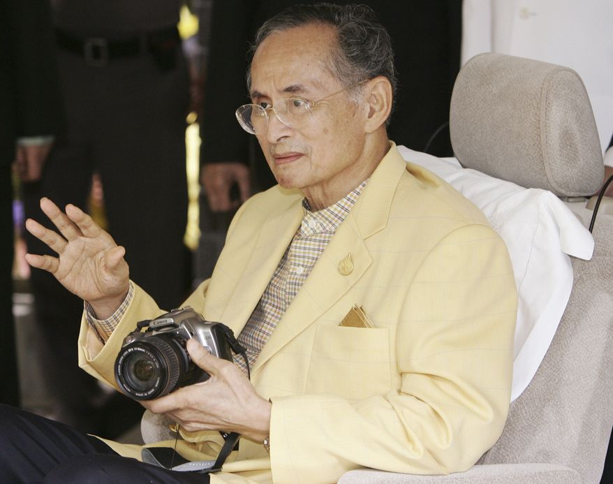 In this Aug. 4, 2006, file photo,Thailand's King Bhumibol Adulyadej holds a camera as he waves while leaving Siriraj Hospital in Bangkok. Thailand's Royal Palace said on Thursday, Oct. 13, 2016, that Thailand's King Bhumibol Adulyadej, the world's longest-reigning monarch, has died at age 88. (AP Photo/Sakchai Lalit, File)