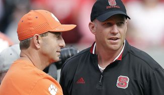 FILE - In this Oct. 31, 2015, file photo, Clemson coach Dabo Swinney, left, and North Carolina State coach Dave Doeren chat before an NCAA college football game in Raleigh, N.C. NC State is looking to turn the Atlantic Coast Conference from a runaway into a free-for-all.  Halfway through the season, powerhouse No. 3 Clemsonis a heavy favorite for a second straight ACC title and berth in College Football Playoffs. But the Tigers' path back, starting with the Wolfpack on Saturday, is crowded with ACC speed bumps, both in the Atlantic and Coastal divisions. (AP Photo/Gerry Broome, File)