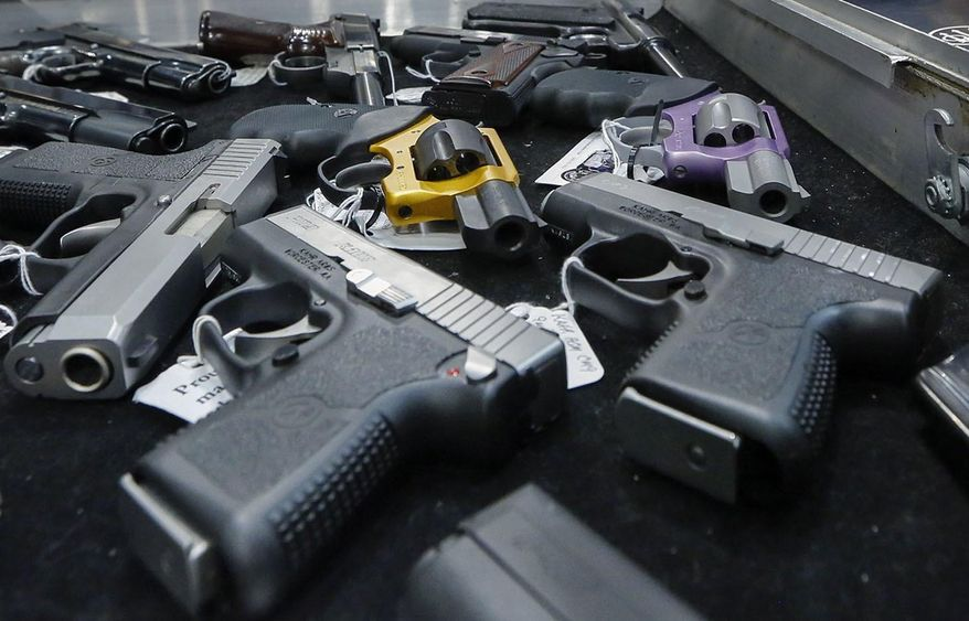 Handguns are displayed on a vendor's table at an annual gun show in Albany, N.Y., on Jan. 26, 2013. (Associated Press) **FILE**