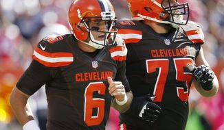 FILE - In this Oct. 9, 2016, file photo, Cleveland Browns quarterback Cody Kessler (6) walks off the field with Joel Bitonio after being injured on a hit by New England Patriots outside linebacker Dont'a Hightower in the first half of an NFL football game, in Cleveland. The Browns (0-5) and Titans  (2-3) play Sunday, Oct. 16, 2016.(AP Photo/Ron Schwane, File)