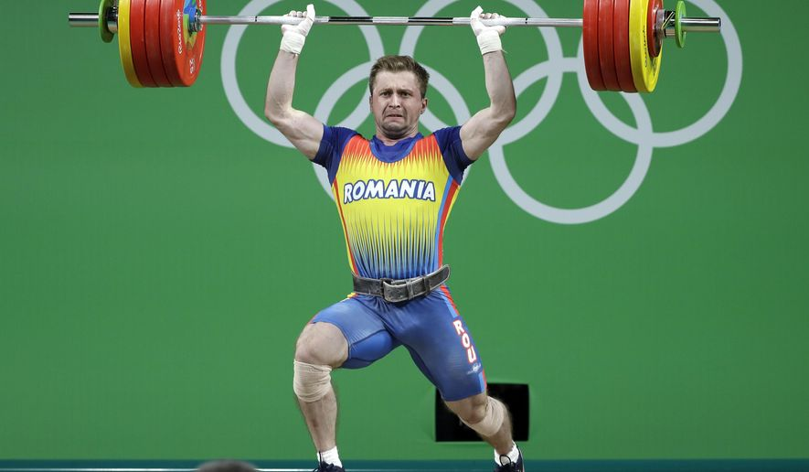FILE- In this Friday, Aug. 12, 2016 file photo, Gabriel Sincraian, of Romania, competes in the men's 85kg weightlifting competition at the 2016 Summer Olympics in Rio de Janeiro, Brazil. The International Weightlifting Federation says Sincraian, who won a bronze medal at the Rio de Janeiro Olympics, will lose his medal after failing a doping test. (AP Photo/Mike Groll, File)
