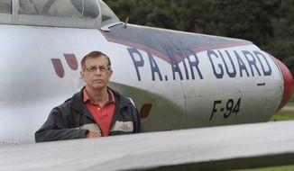 In this Oct. 6, 2016 photo, Joe Monaco, sales manager at Erie County Memorial Gardens, poses with a Korean War-era Lockheed F-94 Starfire jet, which has been a landmark in the veterans section of the Summit Township, Erie County, Pa., cemetery for more than 50 years. Monaco is searching for someone to maintain the landmark. (Jack Hanrahan  /Erie Times-News via AP)