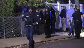 Police search for a suspect after a shooting in the East Boston neighborhood of Boston, Wednesday, Oct. 12, 2016. Police say two officers were shot late Wednesday night. Their conditions were not immediately available. It's unclear what led to the shooting. (AP Photo/Charles Krupa)