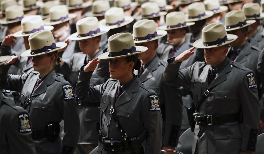 Graduating New York State Police salute during a ceremony at the Empire State Plaza Convention Center on Thursday, Oct. 13, 2016, in Albany, N.Y. The 204th basic school session graduated about 200 new troopers. (AP Photo/Mike Groll)