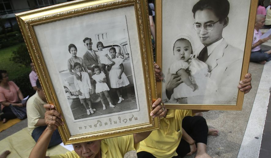 Thais hold portraits of Thai King Bhumibol Adulyadej at Siriraj Hospital where the king is being treated in  Bangkok, Thailand, Thursday, Oct. 13, 2016.  Thais chanted prayers Wednesday as the country's stock market and currency tumbled and the prime minister canceled an overseas trip amid concerns about long-ailing King Adulyadej's health. (AP Photo/Sakchai Lalit)