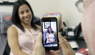 In this June 29, 2015, file photo, Lauren Simo, left, answers questions during a weekly forum streamed via Periscope on the smartphone of Toby Srebnik, Fish Consulting director of social media, at the company's offices in Hollywood, Fla. (AP Photo/Alan Diaz, File)