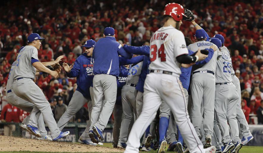 As Washington Nationals' Bryce Harper (34) walks from the field, the Los Angeles Dodgers celebrate a 4-3 win in Game 5 of a baseball National League Division Series, at Nationals Park early Friday, Oct. 14, 2016, in Washington. (AP Photo/Pablo Martinez Monsivais)