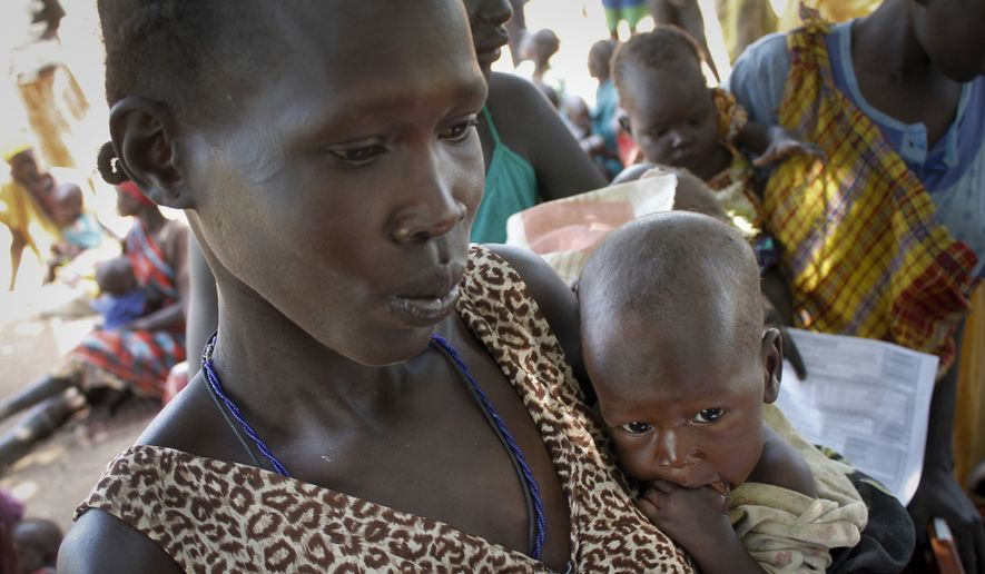 In this photo taken on Friday, Sept. 16, 2016, Elizabeth Athiel holds her 8-month-old malnourished daughter Anger, at a UNICEF clinic in Aweil, South Sudan. Between 4 and 5 million people are at risk of death if they do not receive food assistance, according to the World Food Program, and even as the government has repeatedly promised full humanitarian access to this and other areas, South Sudanese officials have restricted aid amid their hostility at the international community. (AP Photo/Justin Lynch)