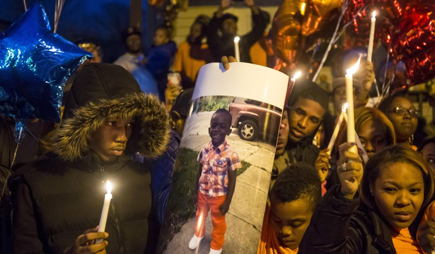 In this Monday, March 21, 2016 photo, family, neighbors and community members gather to remember Devon Lofton, 7,  in front of the house where he lived and died in Englewood, Ill., after being accidentally shot. Forty-two times in a 2 1/2 year span a child was killed or injured in an accidental shooting in Illinois.  (Brian Cassella  /Chicago Tribune via AP)
