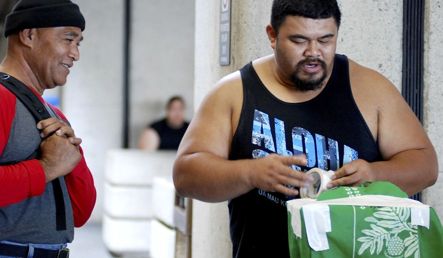 In this Oct. 10, 2016 photo, Mua Migi, left, watches his son Atimua Migi put tape on a carry-on bag before boarding a Hawaiian Airlines flight to Pago Pago, American Samoa at Honolulu International Airport in Honolulu. Atimua Migi doesn't like the airline's new policy of assigning seats at the airport after the airline conducted a survey that involved weighing passengers traveling between Pago Pago and Honolulu. (AP Photo/Jennifer Sinco Kelleher)